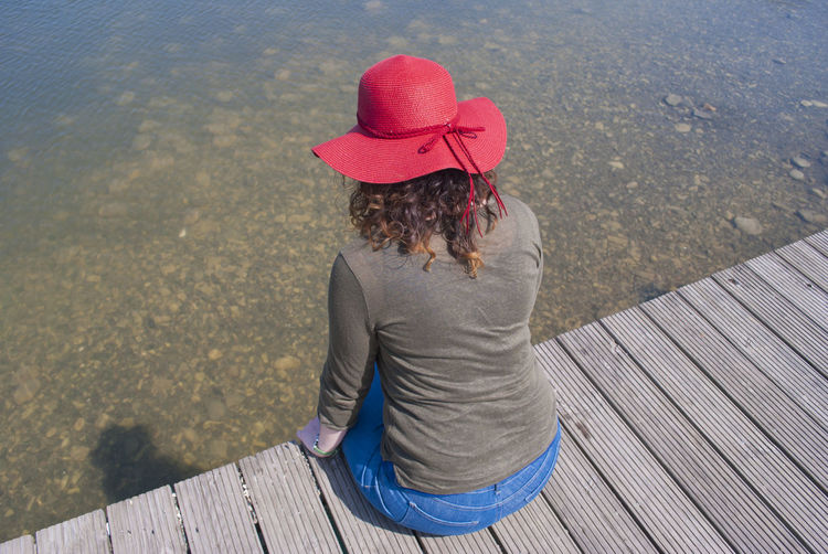 Woman In Red Hat Sitting Against Lake