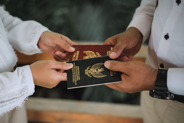 Midsection of people holding passport