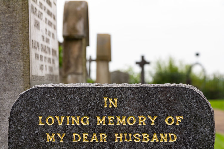 "Gravestone: ""In Loving Memory of My Dear Husband"" Cemetery Death Husband In Loving Memory Architecture Cemetery Close-up Communication Day Emotion Focus On Foreground Grave Gravestone Grief Memorial No People Outdoors Rip Sadness Stone Stone Material Text The Past Tombstone Western Script"