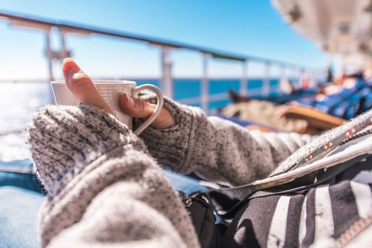 Cup of Coffee on the Cruise Ship Deckchair During Ocean Crossing. Woman Wearing Sweater Holding White Cup of Coffee in Hand. Cruise Ship Cup Of Tea Maritime Tea Close-up Cruise Day Focus On Foreground Human Body Part Human Hand Leisure Activity One Person Outdoors People Real People Ship Transatlantic Crossing Warm Clothing Young Adult