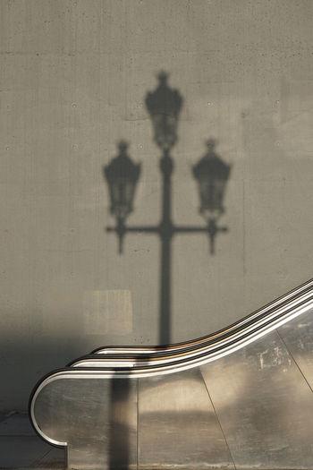 Lantern shadow on railing and wall