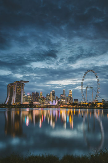 Marina bay sands by bay of water in city at dusk