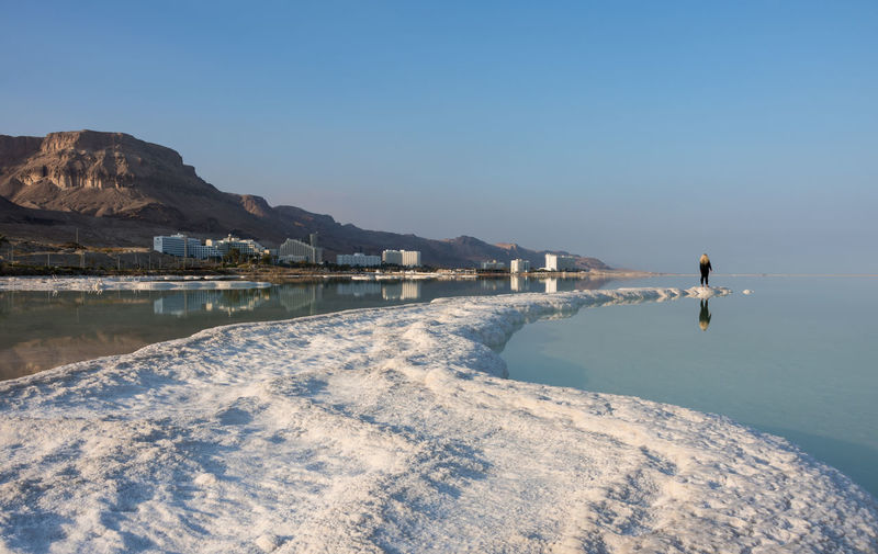 Distant view of woman standing on salt at dead sea against blue sky