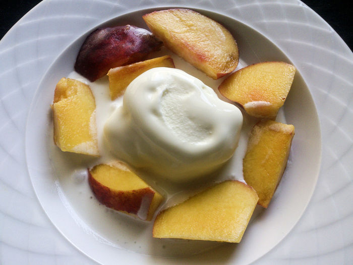 Directly above shot of sliced peach with vanilla ice cream in plate