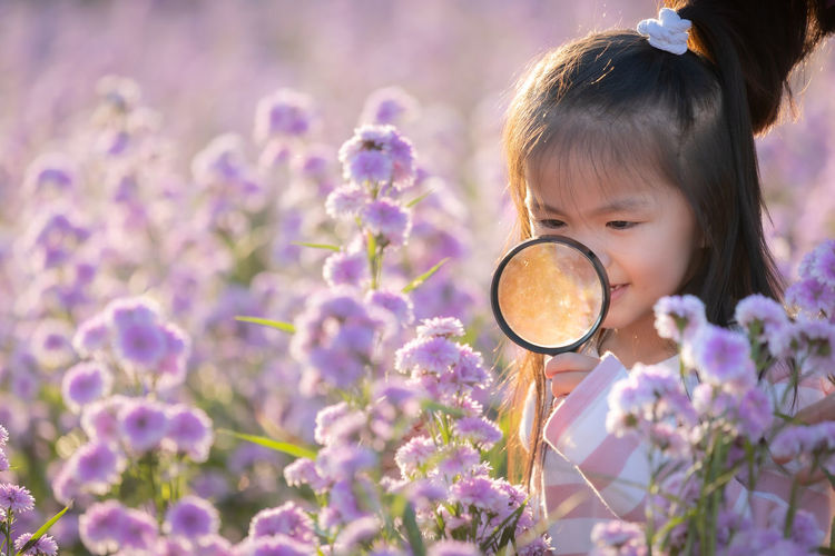 Close-up of girl holding magnifying glass by purple flowering plants