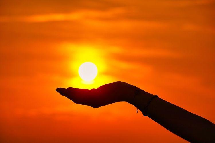 Silhouette hand holding sun against orange sky