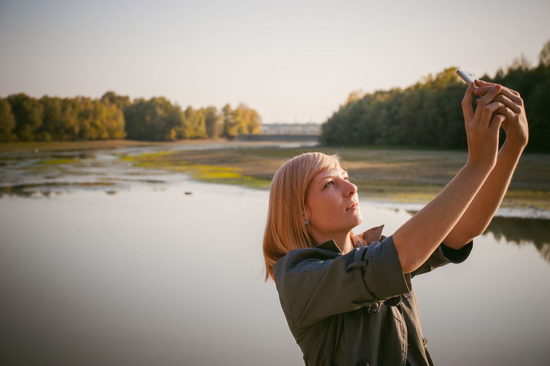 Woman photographing with mobile phone by lake