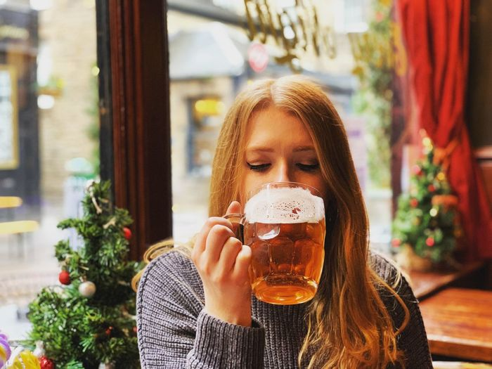 Woman drinking beer in glass at restaurant