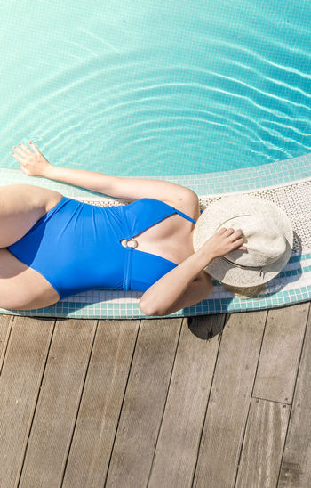 Woman in blue bodysuit resting at poolside