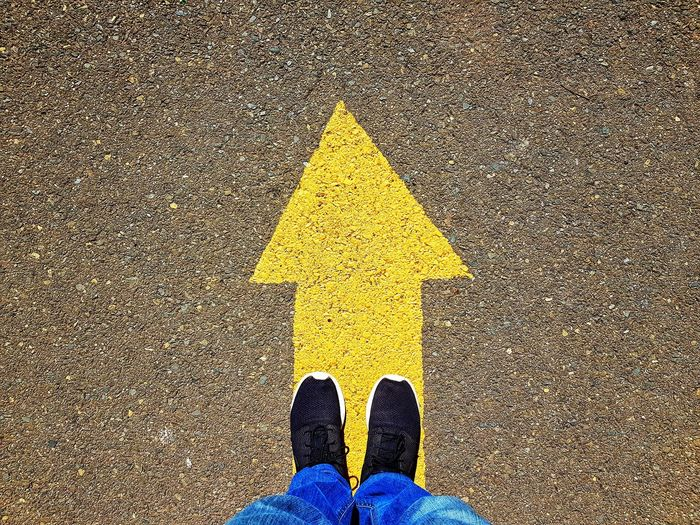 Man xith black shoes standing on a yellow arrow Direction Low Section Standing Yellow Human Leg Shoe Pattern Directly Above High Angle View Personal Perspective Marking Arrow Sign Directional Sign Arrow One Way Information Sign Signboard Flat Shoe Arrow Symbol Road Sign Traffic Arrow Sign