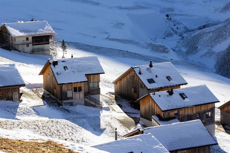 Snow covered houses by buildings against mountain