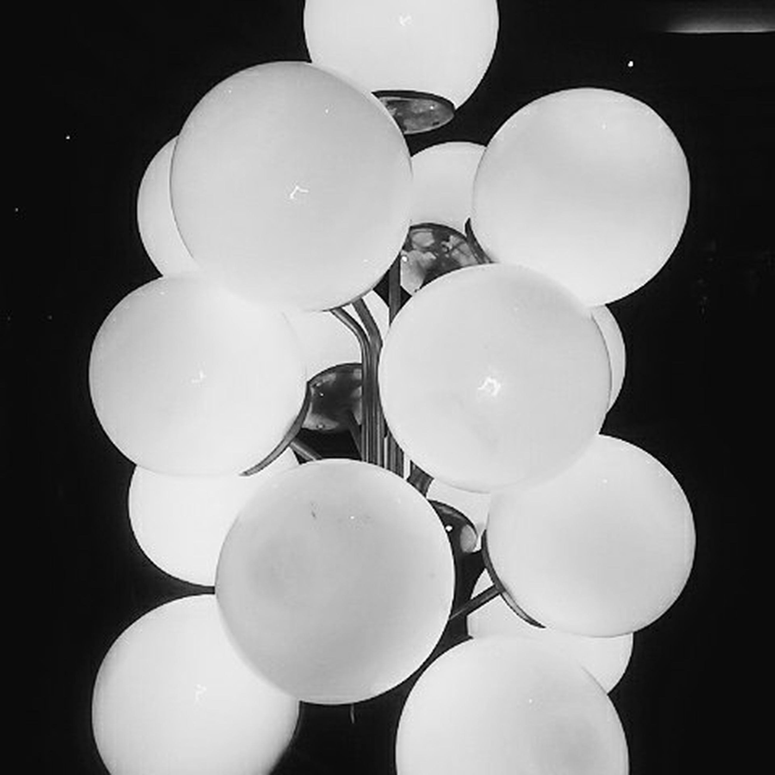 indoors, sphere, circle, night, low angle view, lighting equipment, white color, illuminated, moon, close-up, ceiling, large group of objects, electricity, hanging, no people, shape, geometric shape, dark, electric lamp, black background