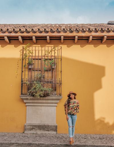 Portrait of woman standing against house