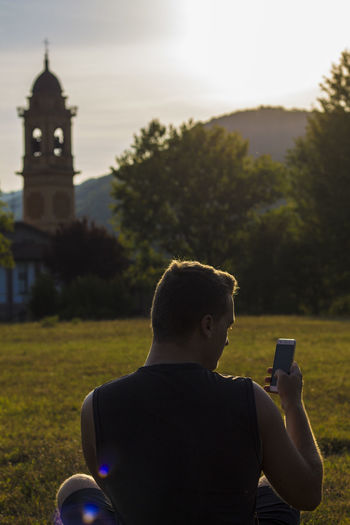 Rear view of man looking at phone in park