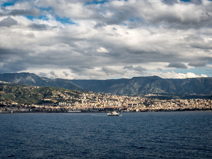 City By Mountains And Sea Against Cloudy Sky