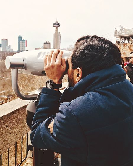 Man looking through coin-operated binoculars in city