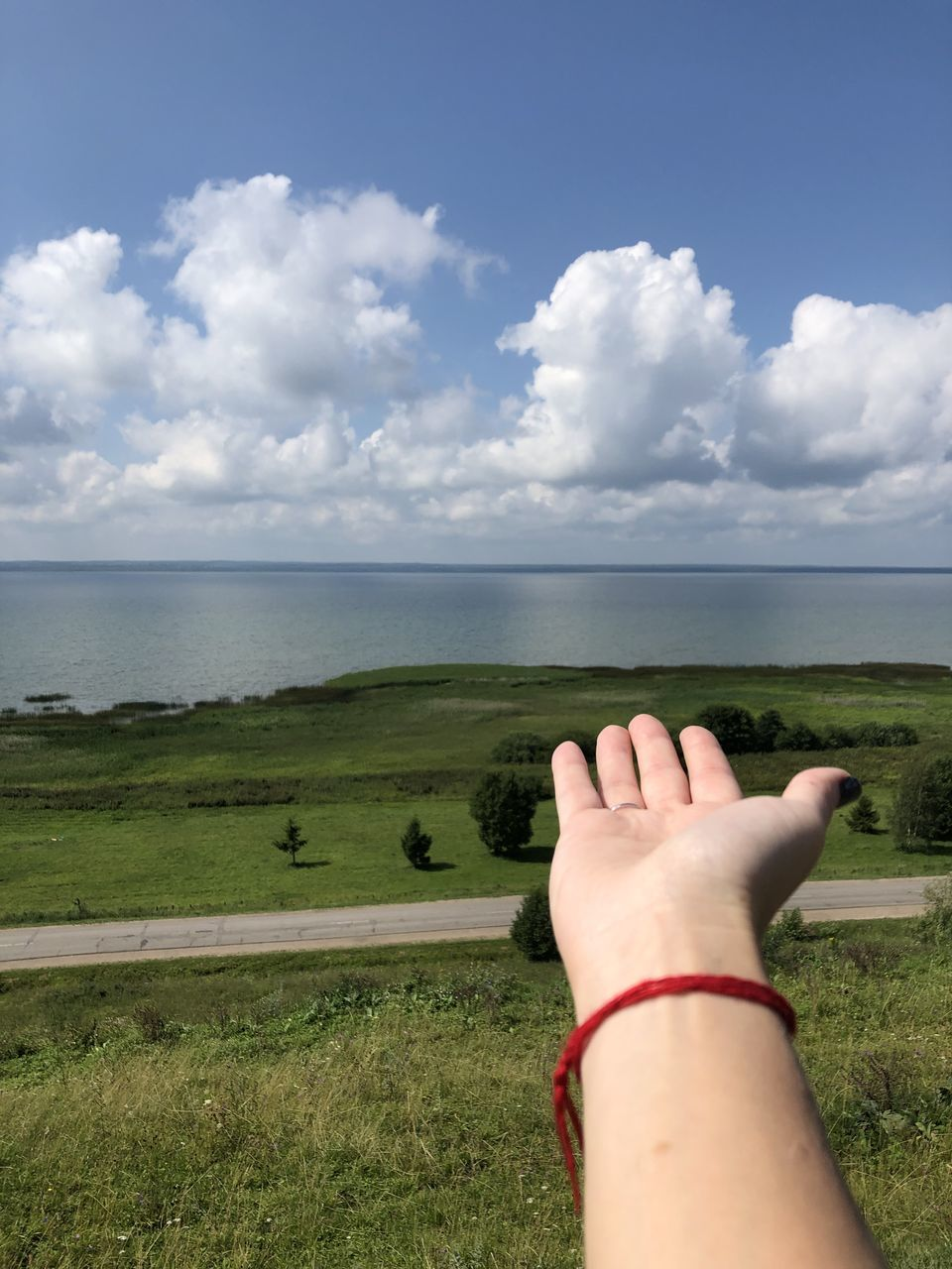 sky, cloud - sky, nature, water, land, plant, grass, human body part, horizon, day, sea, scenics - nature, real people, one person, beauty in nature, personal perspective, horizon over water, human hand, body part, outdoors, hand
