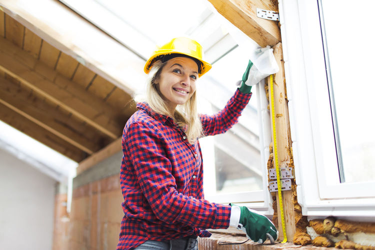 beautiful woman with yellow helmet is working in her loft Architecture Built Structure Casual Clothing Construction Site Construction Worker Day Happiness Hardhat  Headwear Indoors  Lifestyles Looking At Camera Manual Worker Occupation One Person People Portrait Real People Smiling Standing Women Working Young Adult Young Women