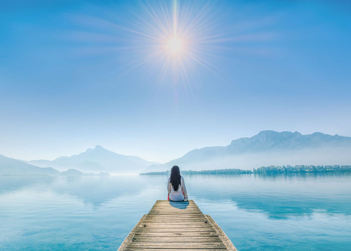 Rear view of woman on pier at lake against sky