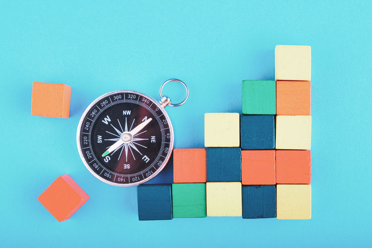 compass and colorful wooden cube on blue background Geometric Shape Indoors  Studio Shot Multi Colored No People Shape Close-up Blue Still Life Direction Toy Design Table Colored Background Guidance Architecture Creativity Cut Out Directly Above Planning Blue Background
