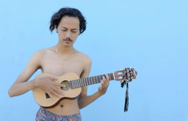 Shirtless man playing guitar against blue wall
