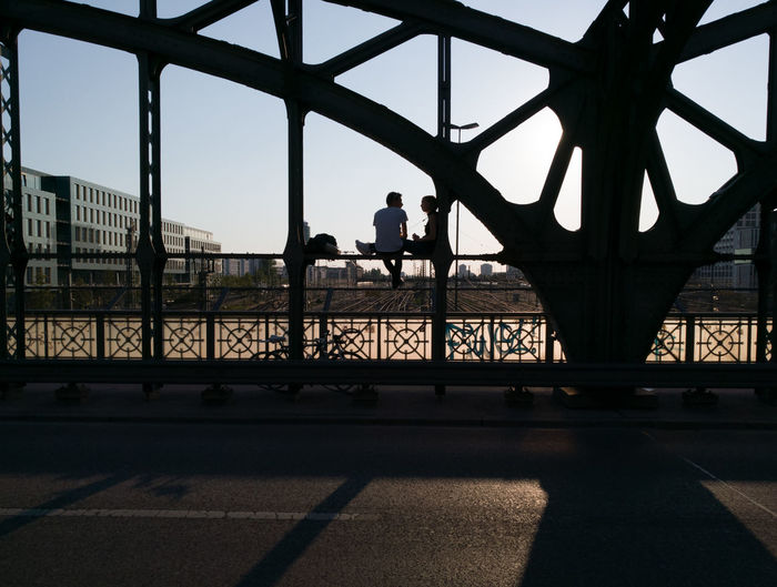 Silhouette people standing on bridge in city against sky