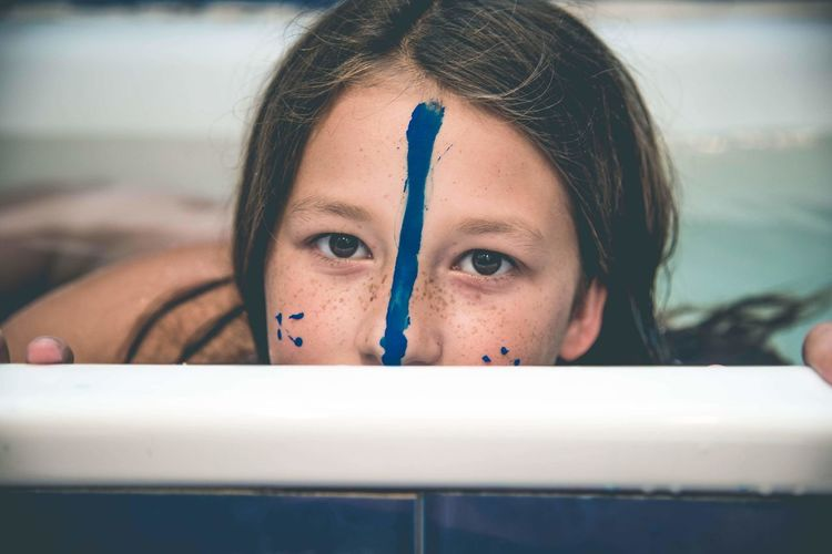 Close-up of sad girl with face paint in bathroom