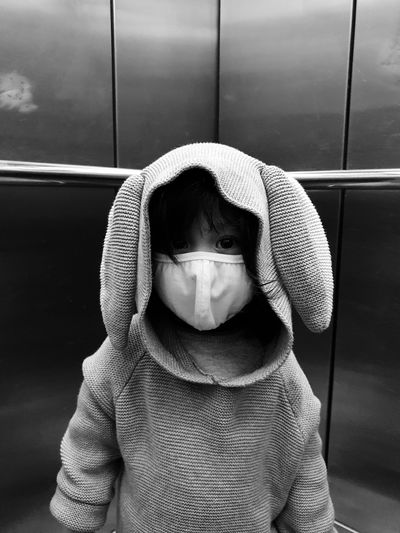 Portrait of cute girl wearing a gray hoodie with rabbit ears