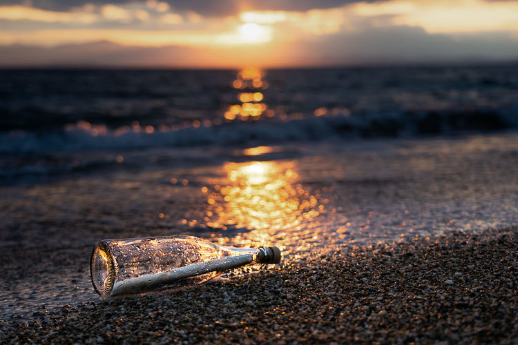 Message in a bottle on a beach at sunset against sky