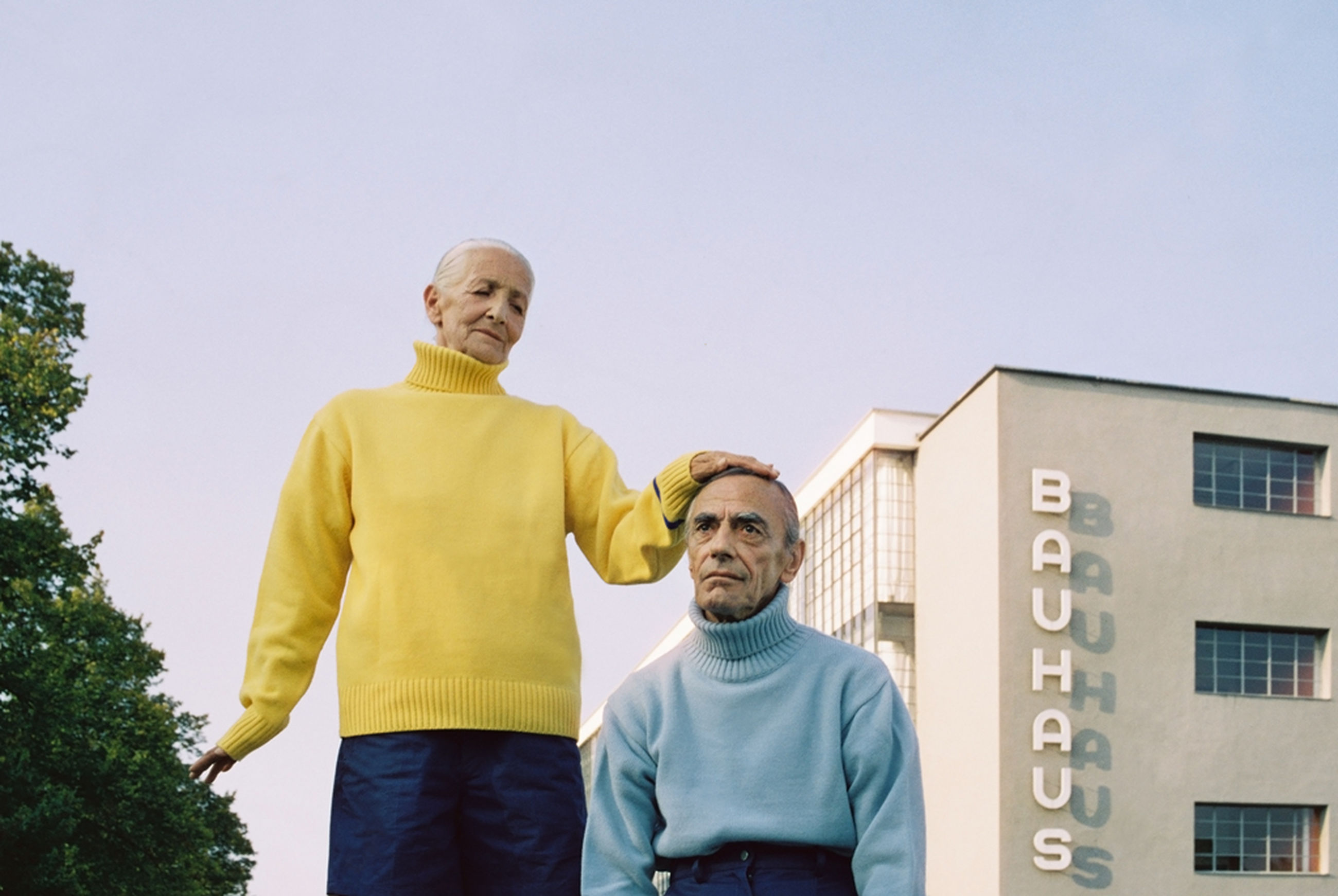 two people, casual clothing, front view, low angle view, real people, house, standing, clear sky, looking at camera, mature men, togetherness, smiling, men, outdoors, lifestyles, day, building exterior, young adult, leisure activity, happiness, father, portrait, young men, built structure, architecture, residential building, yellow, boys, bonding, young women, friendship, sky, adult, people