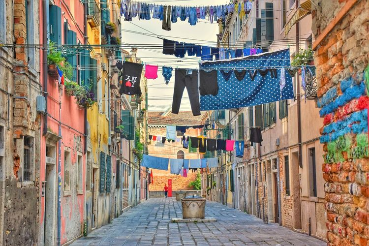 Clothes drying on alley amidst buildings in town