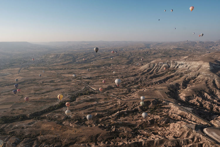 Aerial view of hot air balloons flying over dramatic landscape