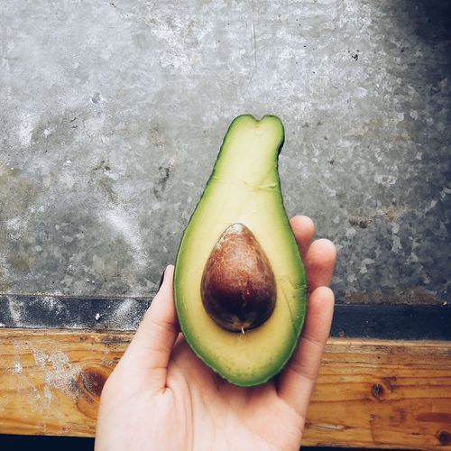 Cropped hand of woman holding avocado against wall