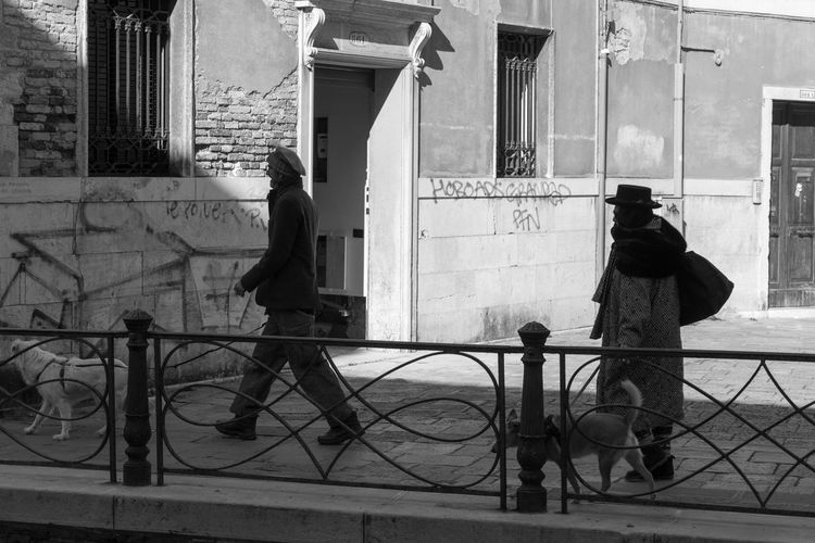 Venetian walk Building Exterior Architecture Built Structure Rear View Full Length City Transportation Mode Of Transportation Real People Two People People Adult Day Street Standing Men Sidewalk Outdoors Dog Venice, Italy Black And White My Best Photo The Art Of Street Photography The Photojournalist - 2019 EyeEm Awards