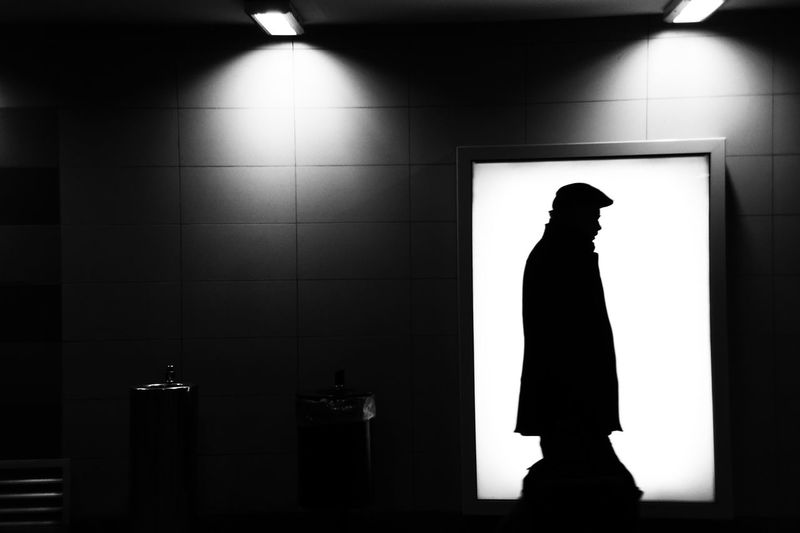 Silhouette man walking against illuminated box at night