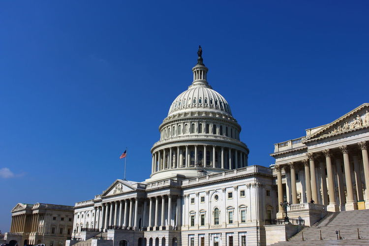 Low angle view of capitol building against clear blue sky