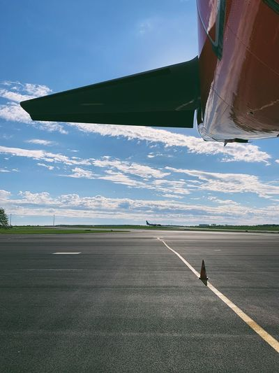 Cropped image of airplane at airport runway against sky