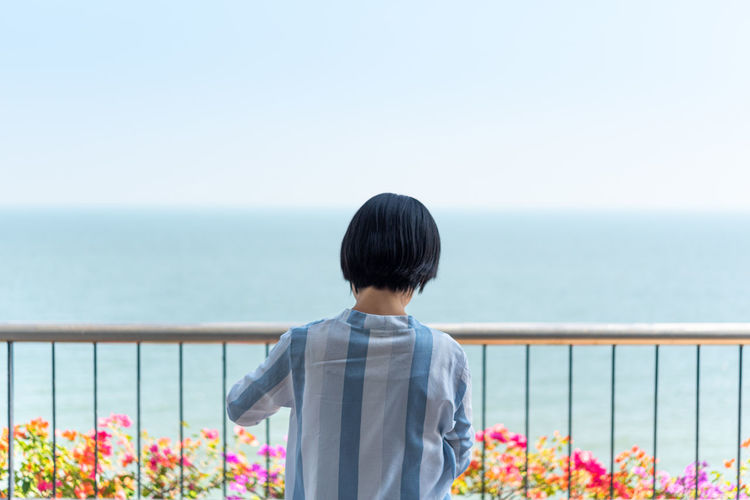 Rear view of person looking at sea against sky