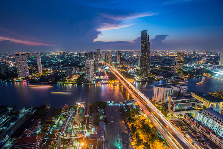 Thailand Bangkok Transportation with Modern Business Building along the river, Hotel and resident area in the capital of Thailand Architecture Building Exterior Built Structure City City Life Cityscape Cloud - Sky Downtown District Growth High Angle View Illuminated Light Trail Long Exposure Modern Motion Night No People Outdoors Sky Skyscraper Speed Travel Destinations Urban Skyline Water