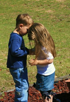 Two kids with their heads together Blond Hair Bonding Boys Casual Clothing Child Childhood Day Elementary Age Friendship Full Length Girls Grass Hands Holding Leisure Activity Nature Outdoors People Real People Sibling Side View Standing Togetherness Two People