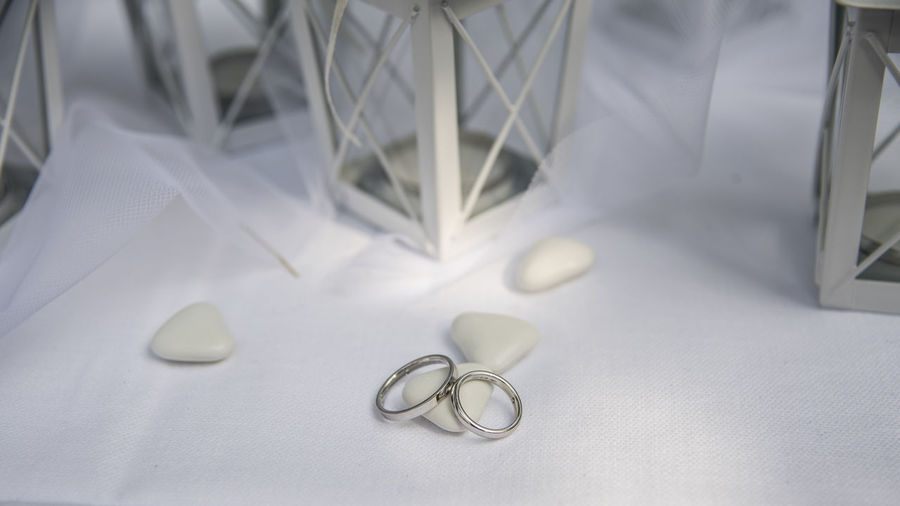 Close up of Wedding rings near comfits and wedding favors Indoors  White Color No People Textile Still Life Wedding Close-up Wedding Ring Table Jewelry High Angle View Ring Celebration Event Focus On Foreground Scissors Metal Selective Focus Healthcare And Medicine Hospital Personal Accessory Silver Colored