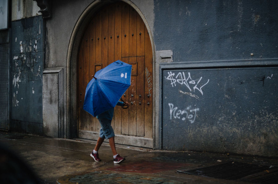 Umbrella boy Full Length One Person Architecture Day Real People Casual Clothing Side View Built Structure Lifestyles Blue Blackboard  Women Standing Building Leisure Activity Text Indoors  Number EyeEm Best Shots EyeEm Selects Streetphotography