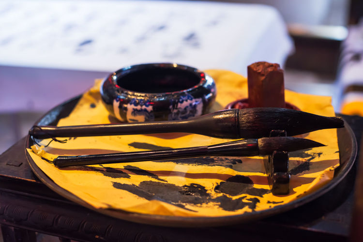 Close-Up Of Calligraphy Brushes On Table