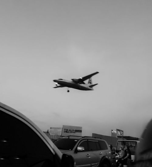 Airplane flying over road in city against sky