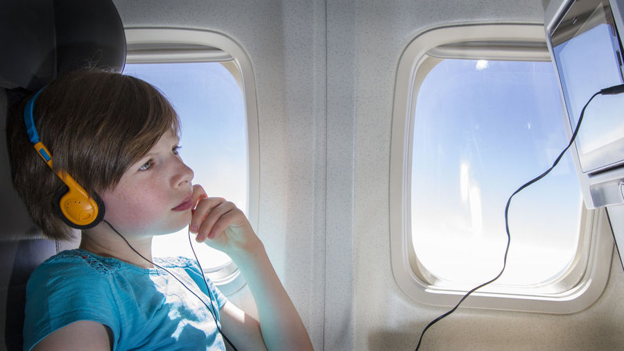 Side view of boy watching television in airplane