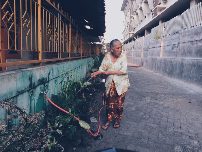Mature woman watering plants at yard