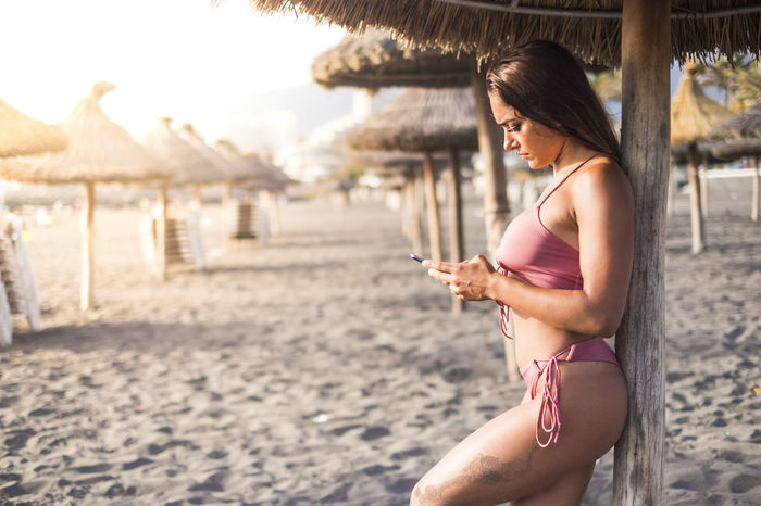 young attractive brunette female use phone at the beach under the umbrella sun during the sunset. golden backlight and connected people concept. vacation on resort in tropical island Relaxing Vacations Adult Beautiful Woman Communication Female Focus On Foreground Hairstyle Holding Leisure Activity Lifestyles Mobile Phone One Person Outdoors Real People Side View Smart Phone Straw Umbrellas Technology Telephone Using Phone Wireless Technology Women Young Adult Young Woman