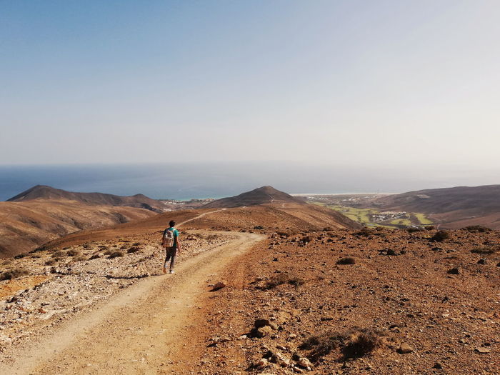 Rear view of man walking on dirt road against clear sky during sunny day