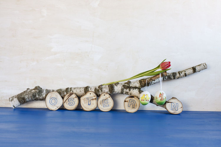 Wooden Decoration With Text On Blue Table Against Wall During Easter