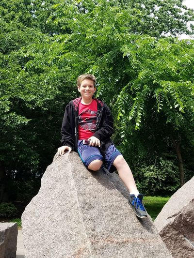 Growing up way too fast. Portrait Of A Son Boy Pre-teen Smile Smiling Happiness Nature Outdoors Casual Clothing One Person One Boy Sitting Full Length Rock Boulder The Great Outdoors - 2017 EyeEm Awards